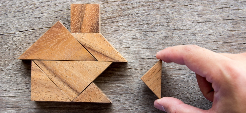 Hand Putting Together Wooden Home Puzzle for Home Process Concept
