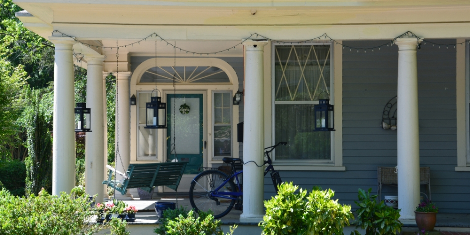 north carolina house blue with covered front porch and a bike