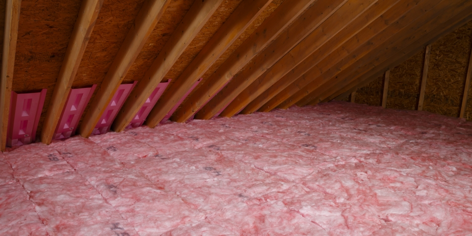 Image of batt insulation installed in an attic with rafter vents installed