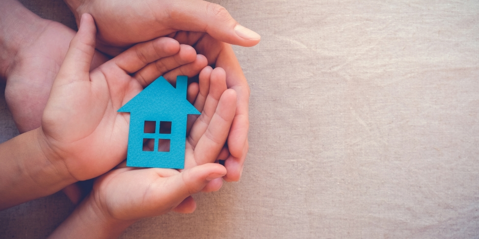Adult and child's hands cupped holding a cutout of a house