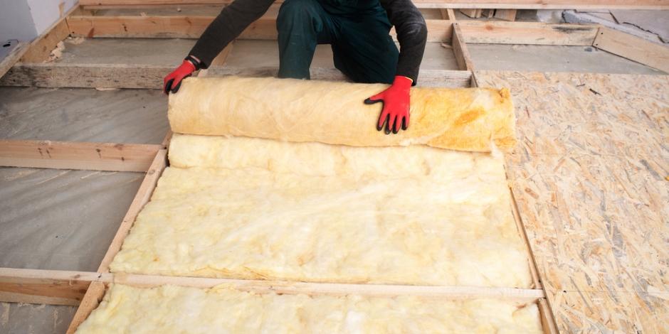 tech installing batt insulation in floor of house